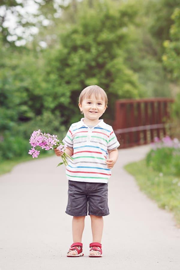Ståenden av ett gulligt förtjusande roligt litet le pojkelitet barn som in går, parkerar med lila purpurfärgade rosa blommor i hä fotografering för bildbyråer