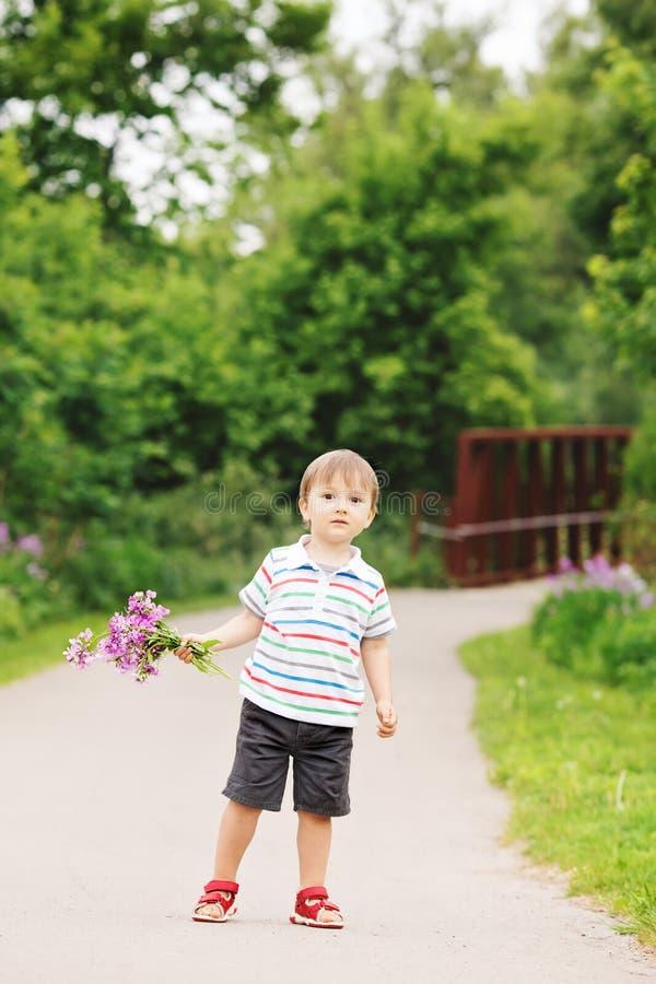 Ståenden av ett gulligt förtjusande roligt litet le pojkelitet barn som in går, parkerar med lila purpurfärgade rosa blommor i hä arkivfoton
