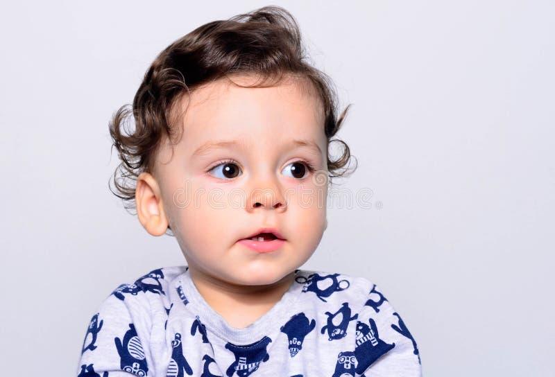 Ståenden av ett gulligt lockigt hår behandla som ett barn pojken som bort ser royaltyfria foton
