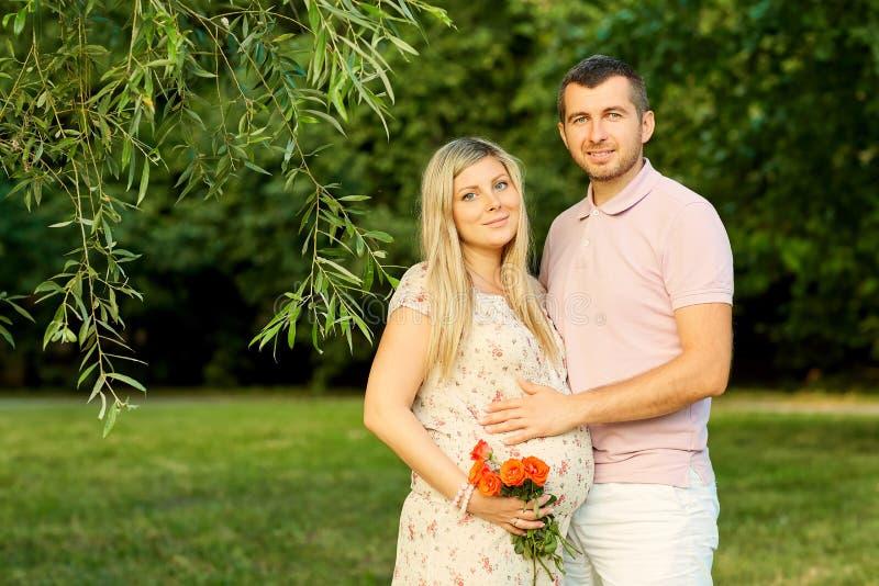 Ståenden av ett härligt gravid par i en sommar parkerar royaltyfri foto