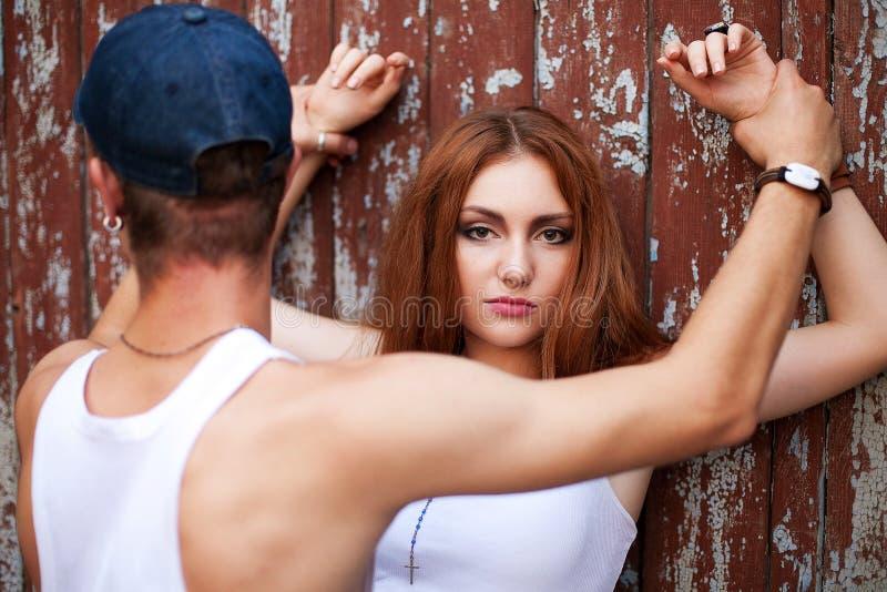 Ståenden av ett härligt ljust rödbrun flickaanseende med en man över uppvaktar arkivbild