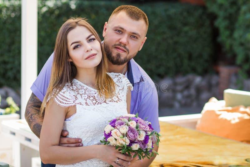 Ståenden av ett romantiskt par mot en bakgrund av gröna buskar och träd, flickainnehav blommar i händer, ung härlig brud royaltyfria bilder