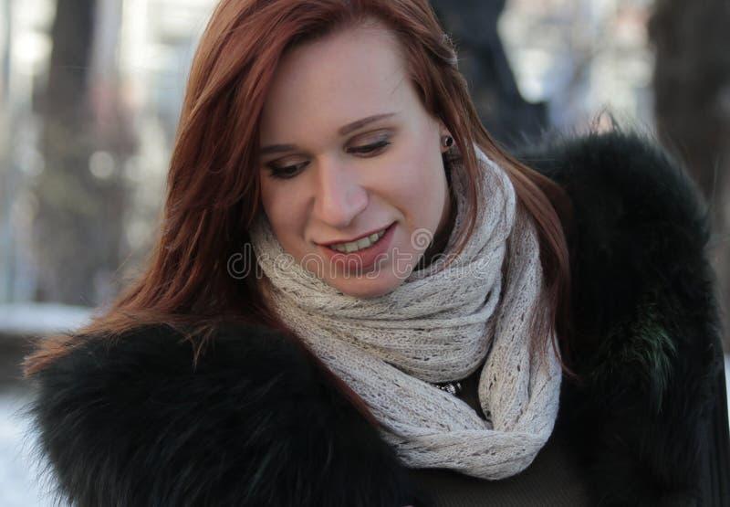 Ståenden av ett ung flickaanseende i parkerar, i vinter och att se ner royaltyfri bild