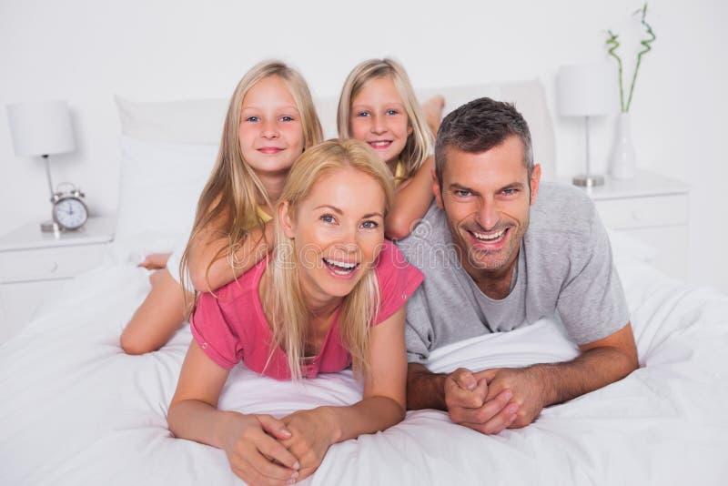 Ståenden av föräldrar som ligger i säng med deras, kopplar samman royaltyfri bild