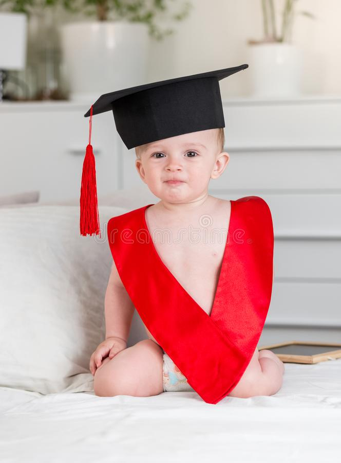 Ståenden av förtjusande behandla som ett barn pojken i akademikermössahatten och det röda bandet som in camera ser Begrepp av tid arkivfoto