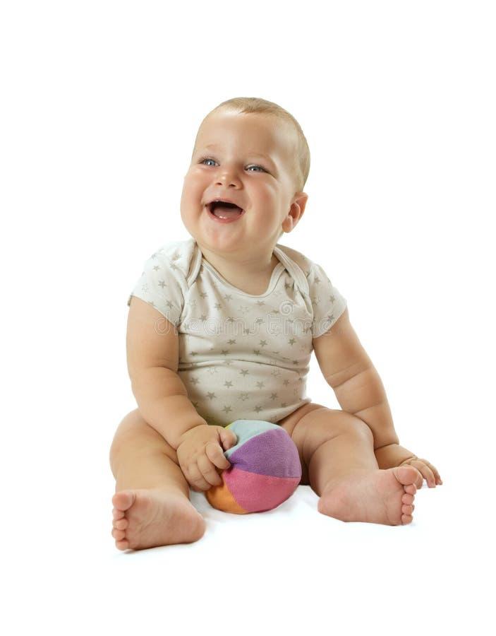 Ståenden av förtjusande behandla som ett barn pojken som placerar på golvet, ler och har gyckel med den färgrika bollen Isolerat  fotografering för bildbyråer
