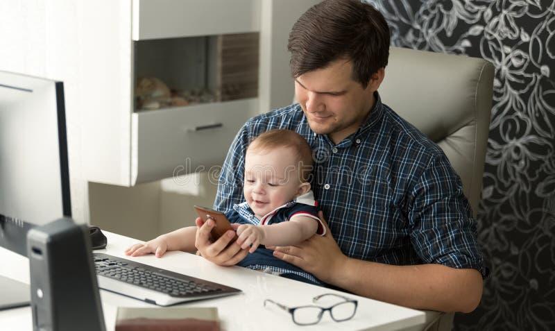 Ståenden av fadern som arbetar på datoren som spelar med hans, behandla som ett barn sonen royaltyfria bilder