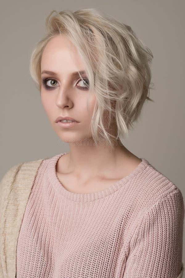 Ståenden av flickan av blondinen med makeup för mörkt öga och kort hår som kastas på en sida, tänder - den rosa tröjan på en ljus arkivbilder