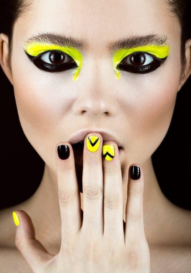 Ståenden av flickan med guling- och svartsmink som är idérik spikar konstdesign Härlig le flicka royaltyfri foto