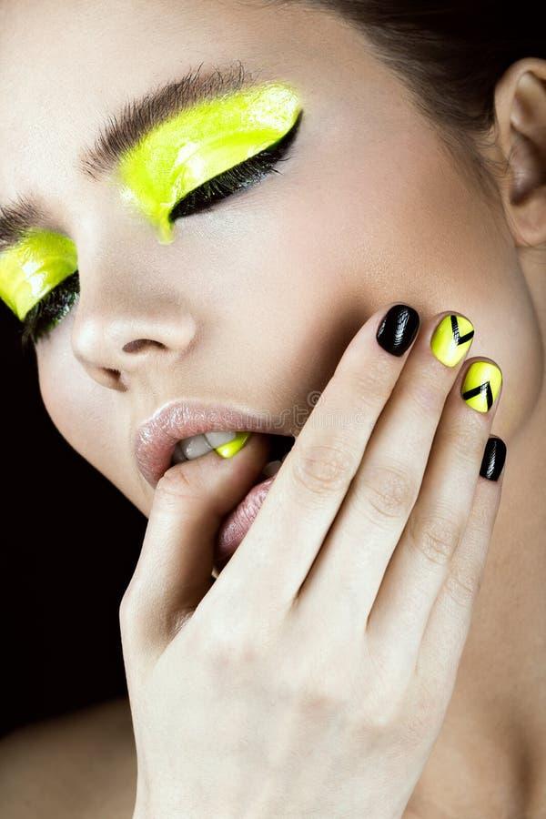 Ståenden av flickan med guling- och svartsmink som är idérik spikar konstdesign Härlig le flicka arkivfoto
