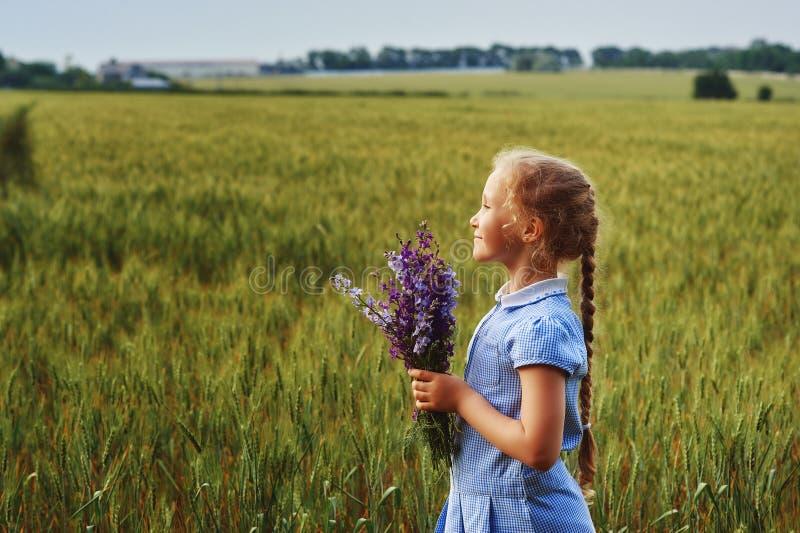Ståenden av flickan på en sommar går lite i fältet arkivfoton