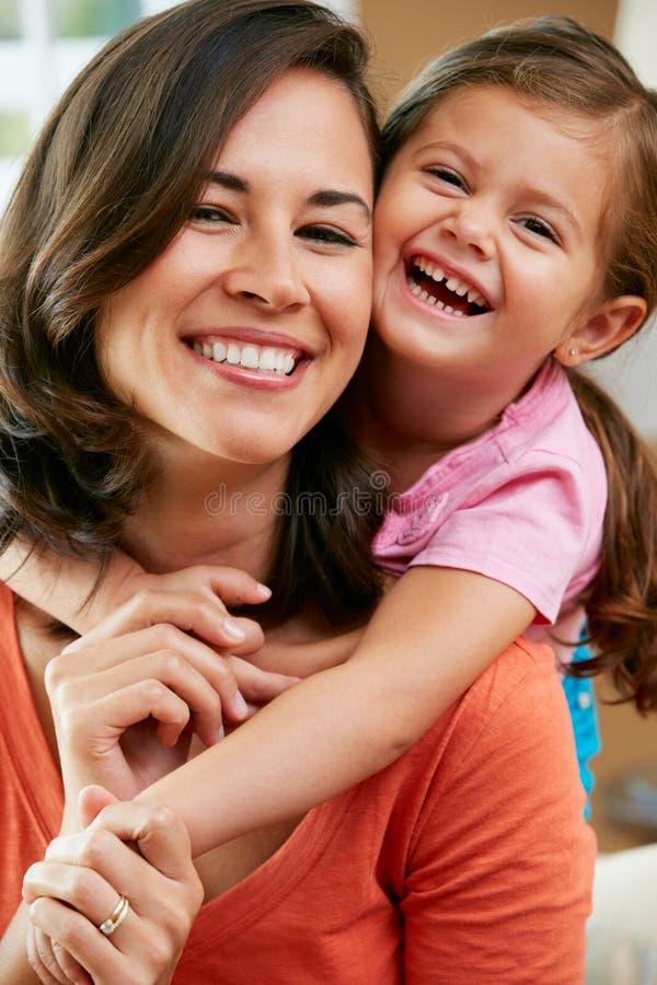 Ståenden av fostrar och dottersammanträde på sofaen hemma royaltyfri bild