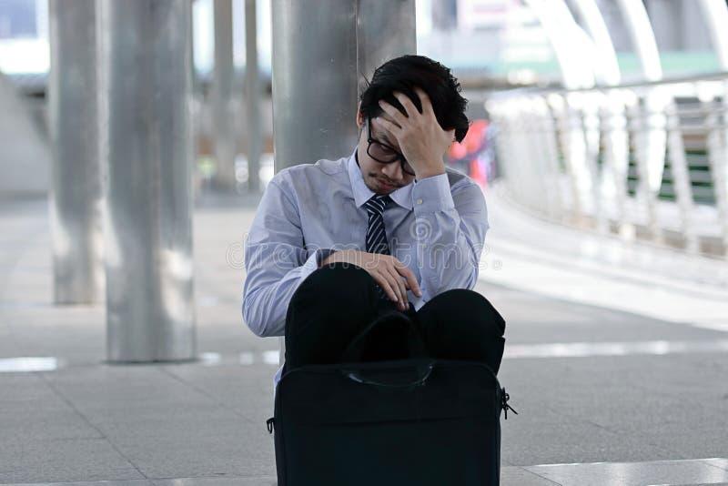 Ståenden av frustrerat stressat ungt asiatiskt mansammanträde på golvet av trottoarkontoret och känsla tröttade med jobb arkivbilder