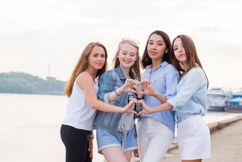 Ståenden av fyra unga studentflickor som visar fingret, gör en gest hjärta royaltyfri fotografi