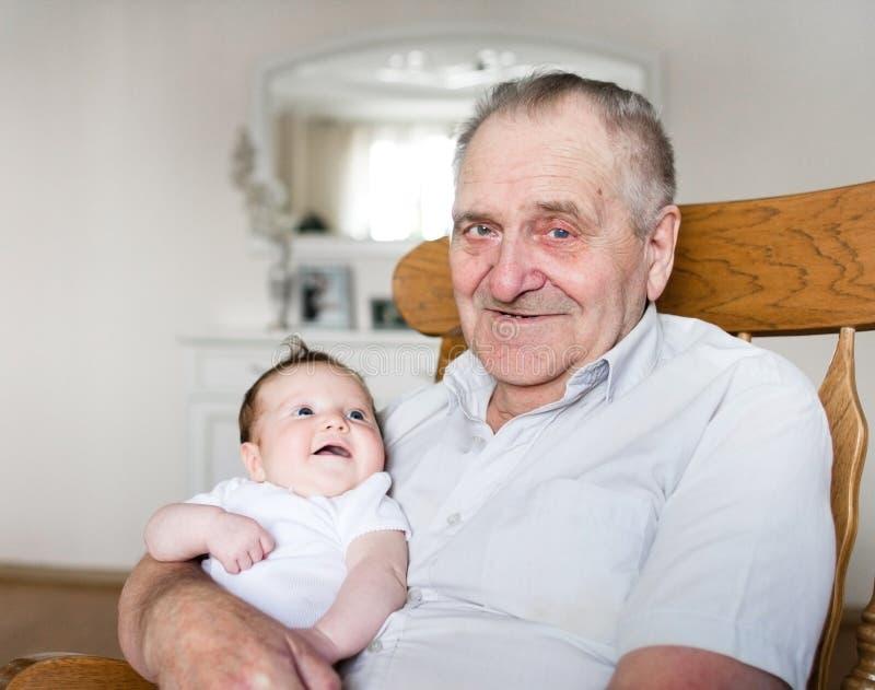 Ståenden av gammelfarfadern som rymmer nyfött, behandla som ett barn royaltyfri foto