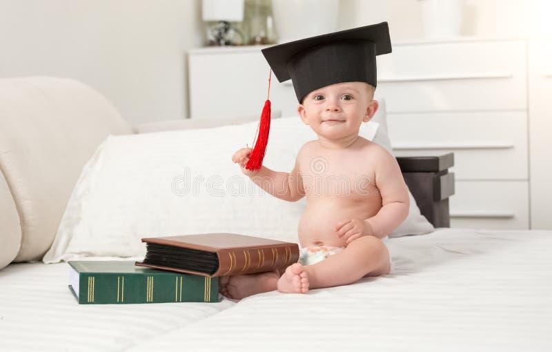 Ståenden av gladlynt behandla som ett barn pojken i svart som avlägger examen på lockplacering royaltyfri bild
