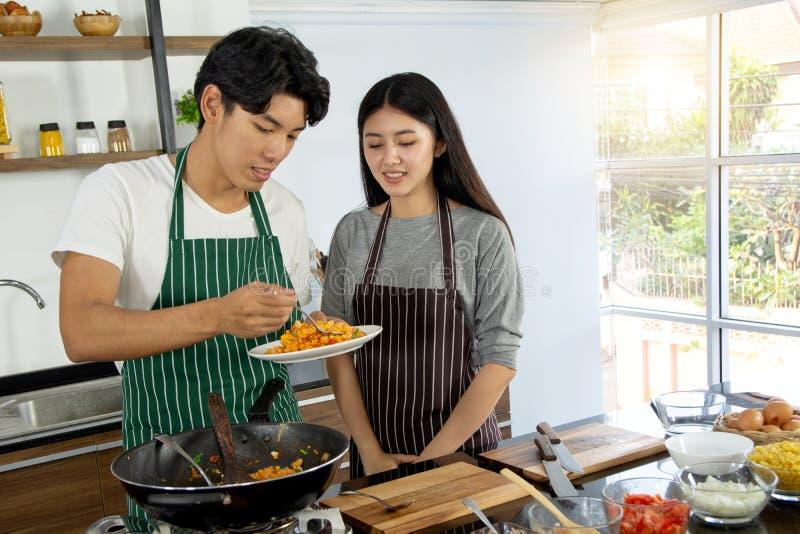 Ståenden av gulliga lyckliga par i förkläde i selfie åtgärdar smaka frukosten av makaroni som dekoreras med ingrediensen och att  arkivfoto