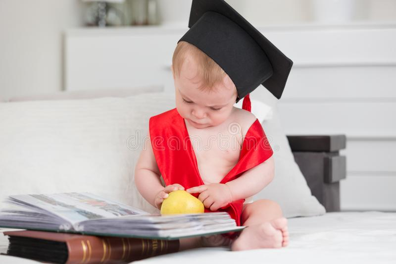 Ståenden av gulligt behandla som ett barn pojken i äpple och läsebok för avläggande av examenlock hållande Begrepp av tidig barnu arkivbilder