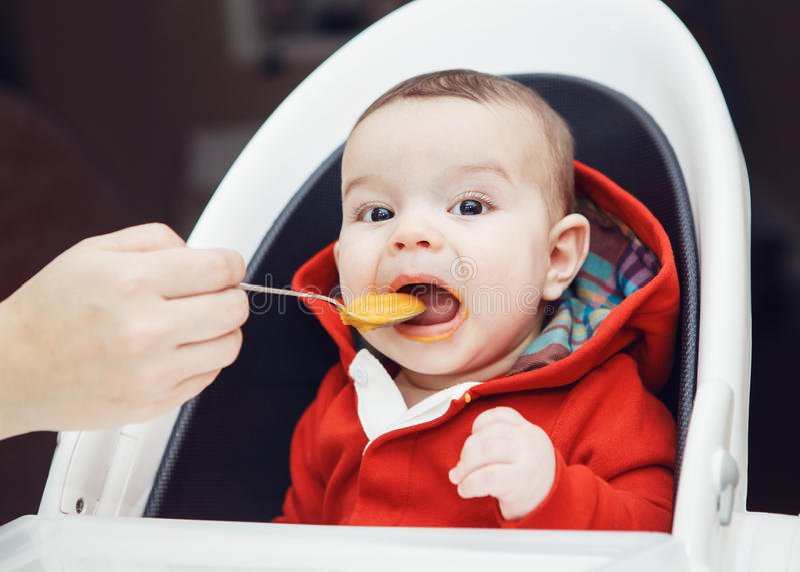 Ståenden av gulligt förtjusande Caucasian litet behandla som ett barn pojkesammanträde i hög stol i kök som äter målpuré royaltyfri bild