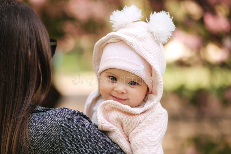 Ståenden av gulligt litet behandla som ett barn flickan utanför med mamman h?rligt flickaleende Fem månad att behandla som ett ba royaltyfria foton