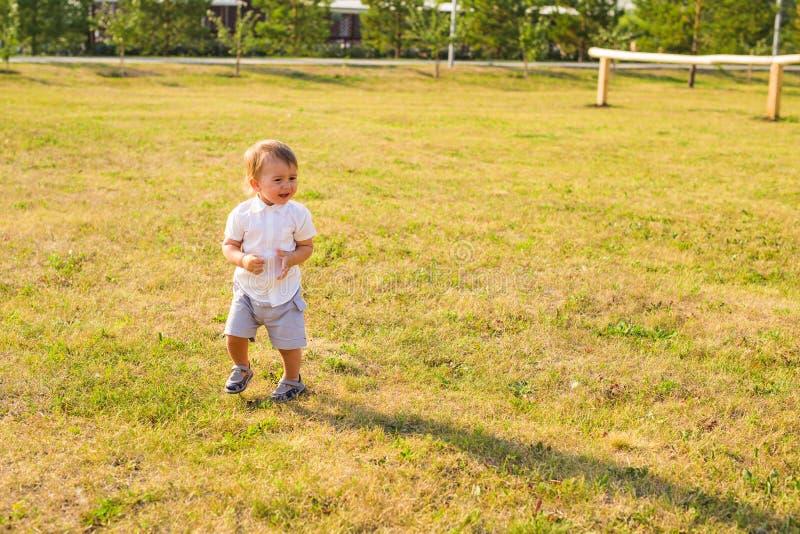 Ståenden av gulligt litet behandla som ett barn pojken som har den roliga yttersidan Le det lyckliga barnet som utomhus spelar arkivbild