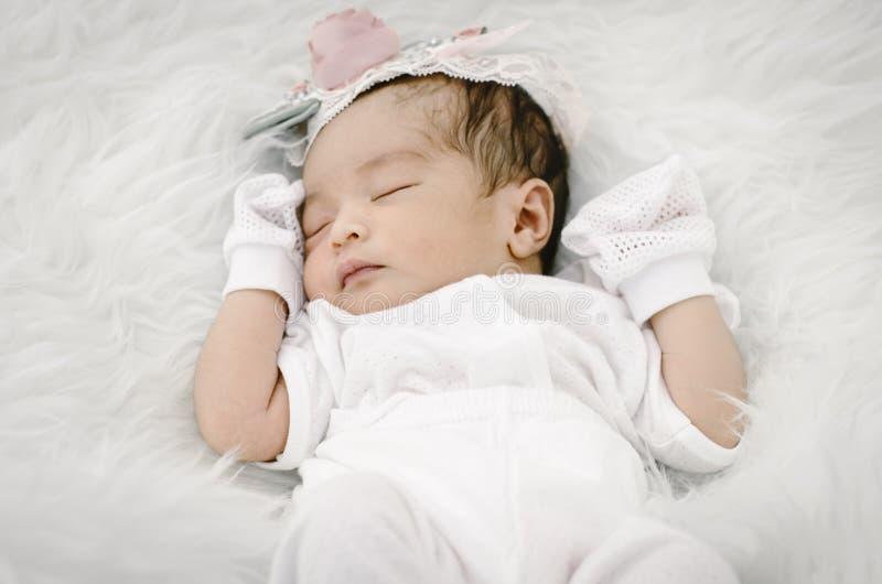 Ståenden av gulligt nyfött behandla som ett barn att sova på den vita filten fotografering för bildbyråer