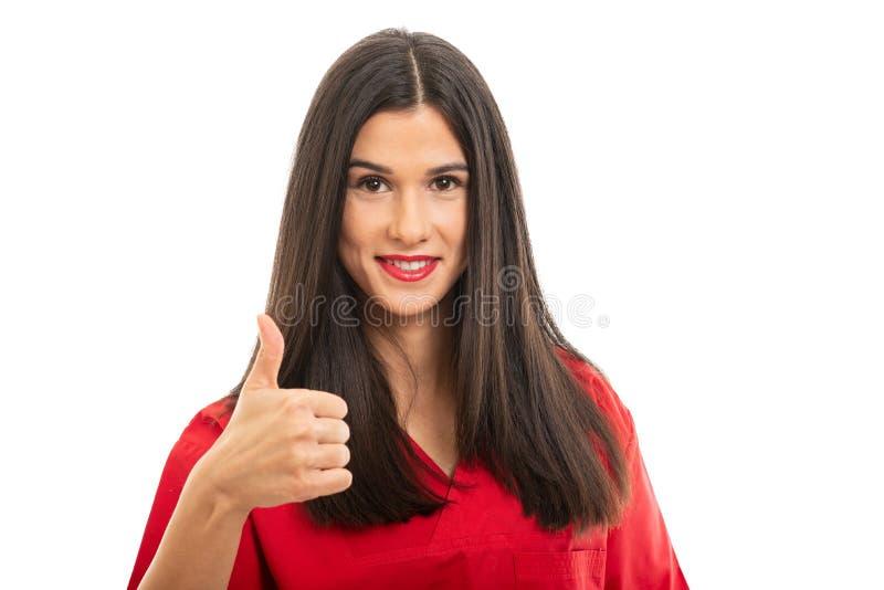 Ståenden av härligt bära för sjuksköterska som är rött, skurar uppvisning av tummen upp royaltyfri fotografi