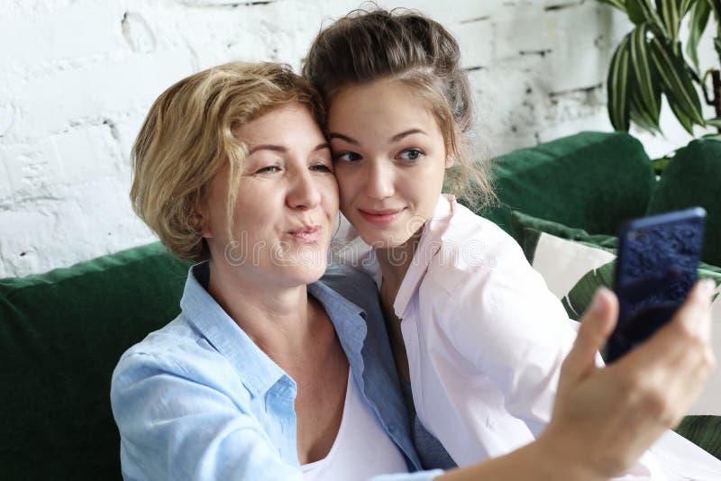 Ståenden av härligt mognar modern och hennes dotter som gör en selfie genom att använda den smarta telefonen och le, hem- och lyc arkivbilder