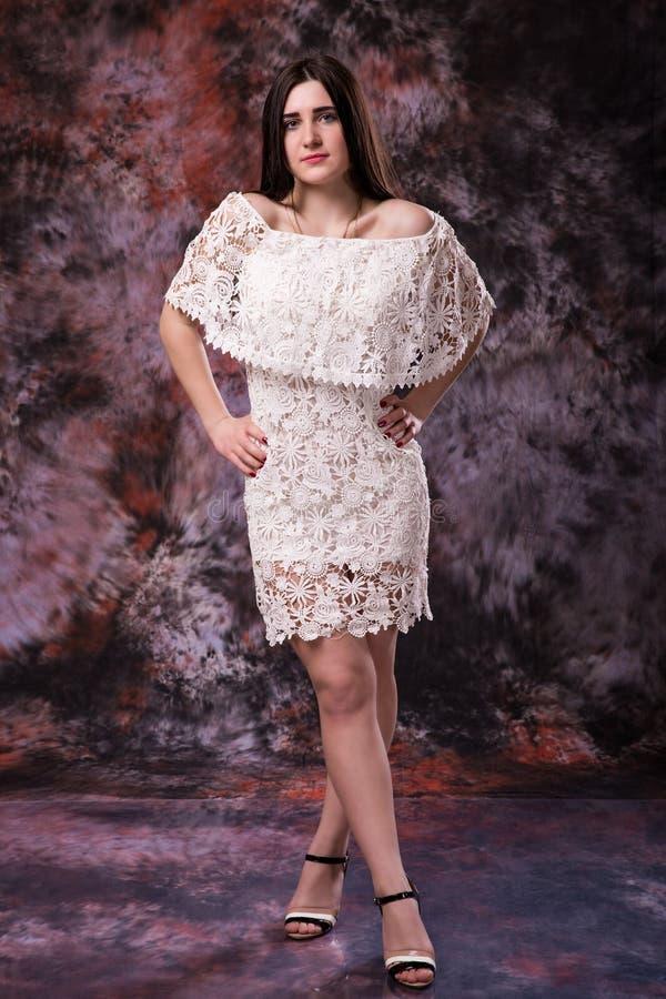 Ståenden av härligt plus lockig ung kvinna för format i den vita klänningen som poserar på marmor, färgade bakgrund arkivfoton