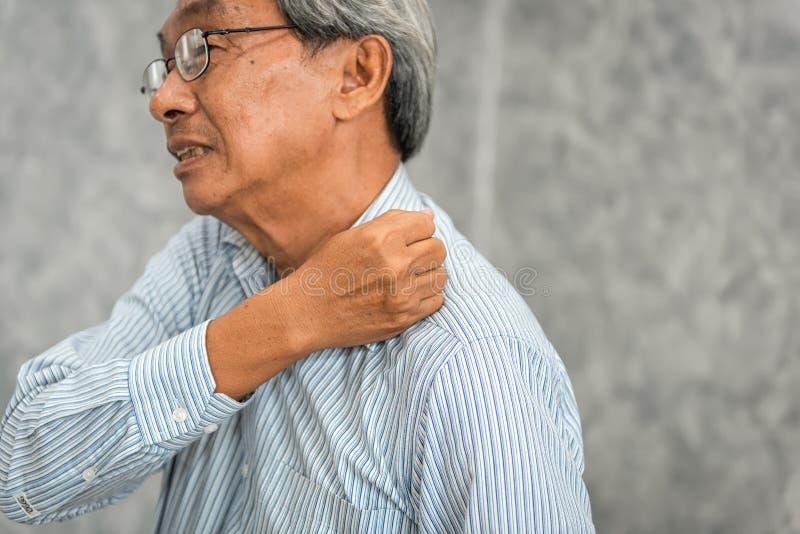 Ståenden av höga mannen som den har, smärtar i hans skuldra, sjukvård a royaltyfri foto