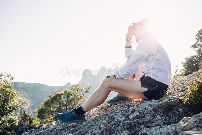 Ståenden av idrottsman nen eller mannen vilar överst av berget royaltyfri foto