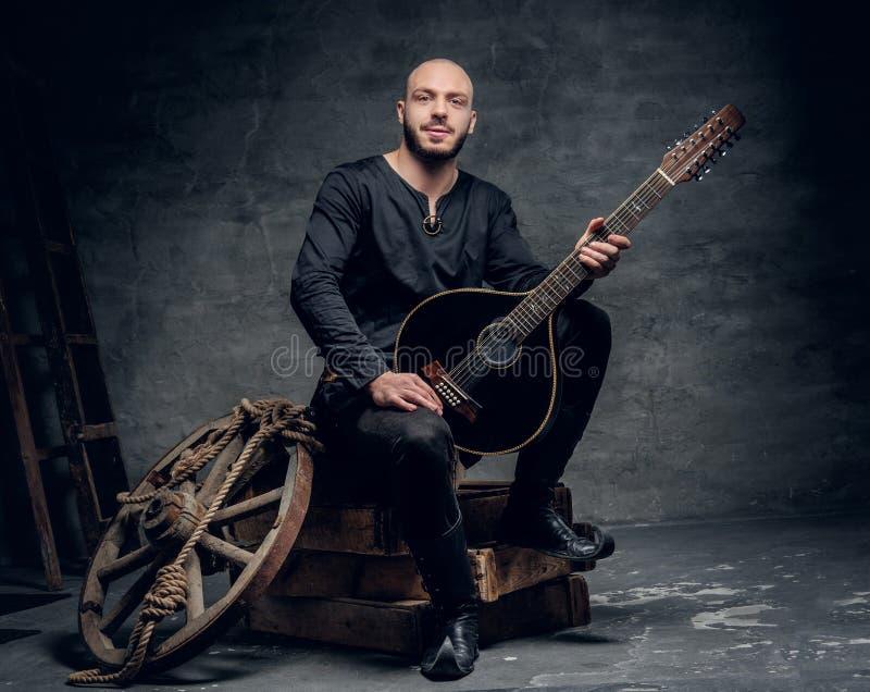 Ståenden av iklädd gammal keltisk kläder för musikern sitter på en träask och att utföra den gamla mandolinen arkivfoto