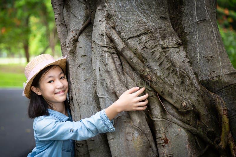 Ståenden av lilla flickan i hatt med att le, att krama den stora trädstammen med armar runt om träd och att se kameran på utomhus royaltyfria foton