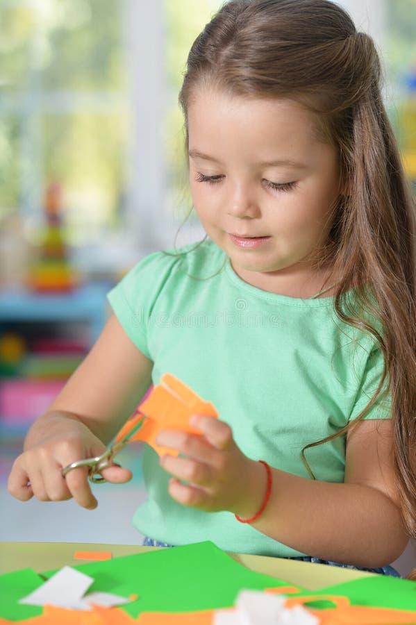 Ståenden av lilla flickan klipper färgpapper fotografering för bildbyråer