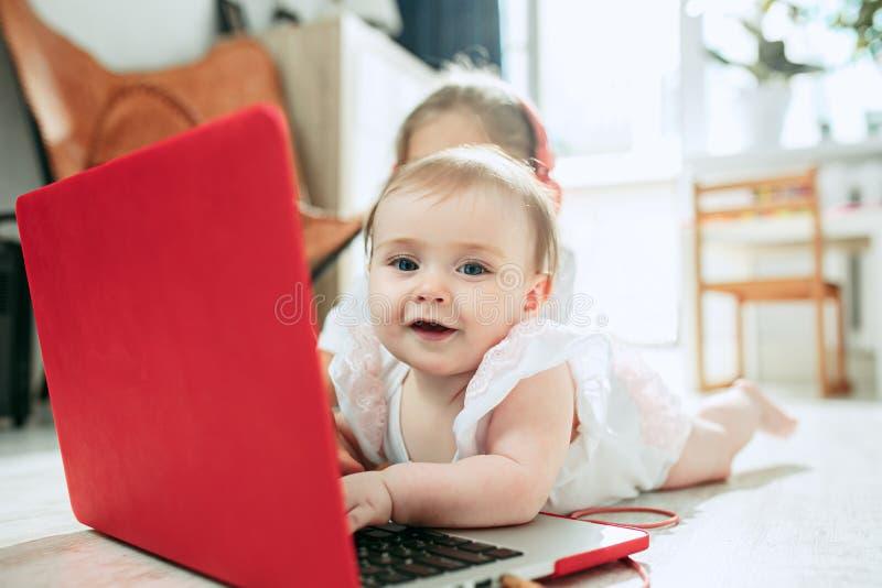Ståenden av lite behandla som ett barn flickan som ser kameran med en bärbar dator royaltyfri bild