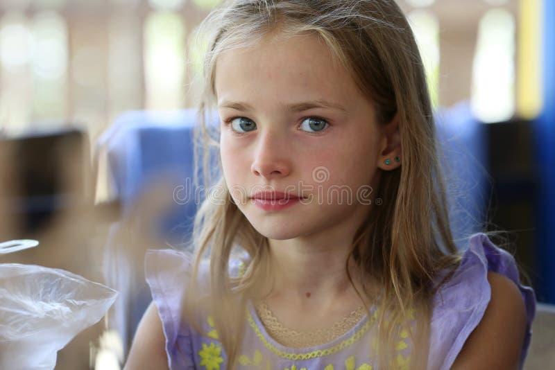 Ståenden av lite flickan med långt hår och blåa ögon av en blondin, som vilar i natur, är allvarligt arkivbilder