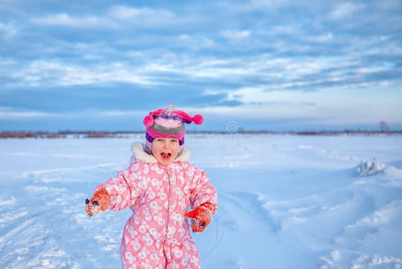 Ståenden av litet gulligt lyckligt behandla som ett barn flickan, går i vintersnö parkerar, arkivbild
