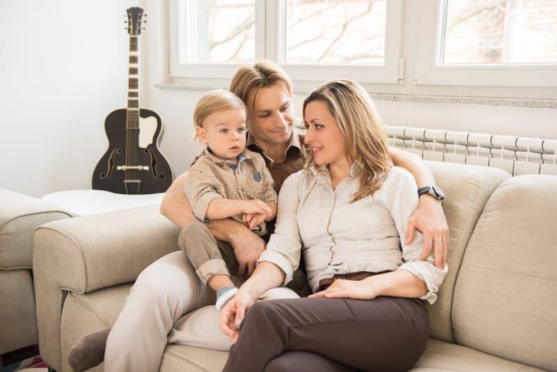 Ståenden av lyckliga föräldrar som sitter på soffan med deras härligt, behandla som ett barn pojken arkivbild