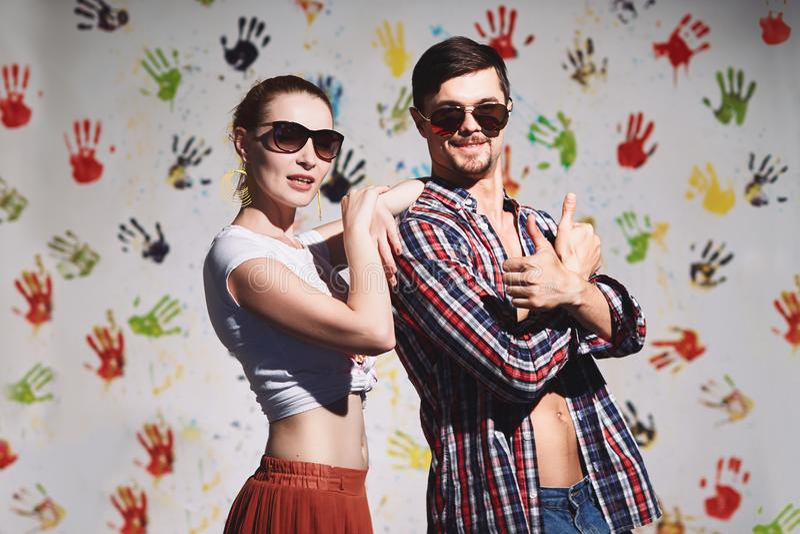 Ståenden av lyckliga par med tummar up tecknet på en rolig positiv bakgrund royaltyfri foto