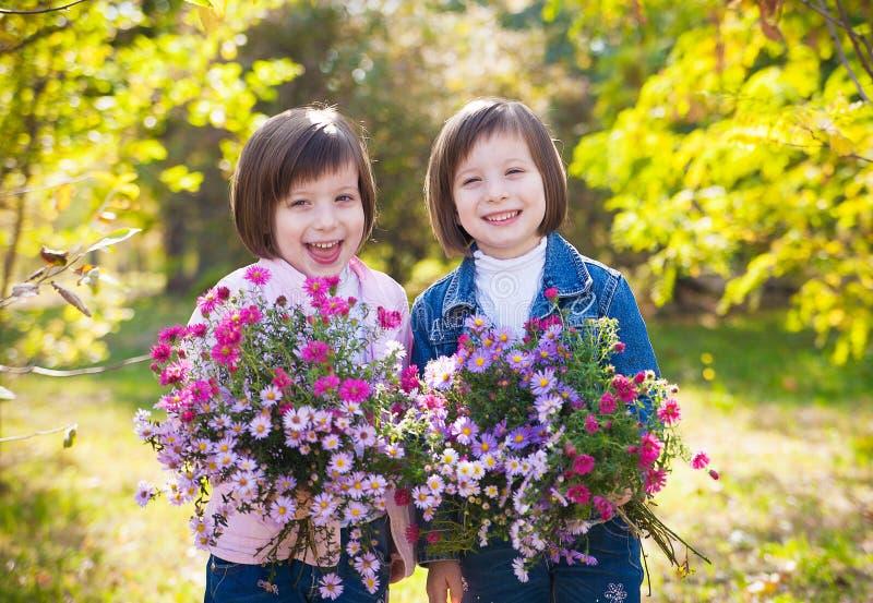 Ståenden av lyckliga två små flickor kopplar samman att koppla av och att tycka om l royaltyfri bild
