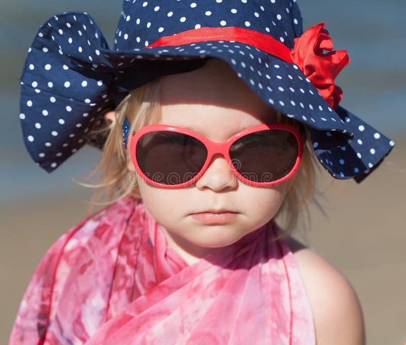 Ståenden av lyckligt behandla som ett barn flickan i hatt och solglasögon arkivbilder