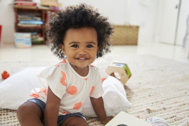 Ståenden av lyckligt behandla som ett barn flickan som spelar med leksaker i lekrum arkivfoton
