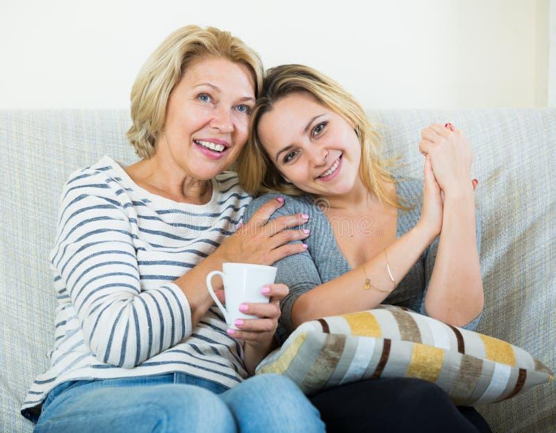 Ståenden av lyckligt mognar modern och barndottern hemma arkivbilder