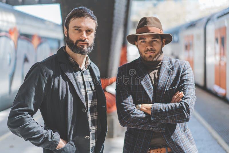 Ståenden av mång--person som tillhör en etnisk minoritet två uppsökte hipsters som tillsammans bär tillfällig kläder och väntar d royaltyfria bilder