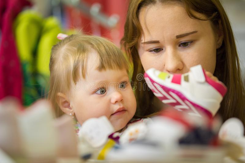 Ståenden av mamman med dottern som väljer skor på barn` s, shoppar royaltyfri bild