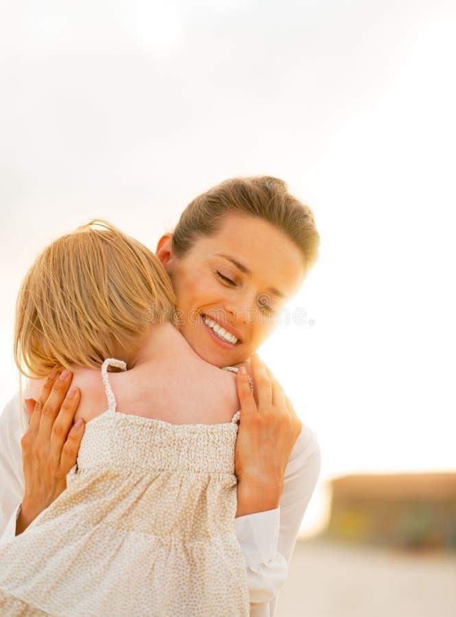 Ståenden av modern och behandla som ett barn att krama för flicka arkivbild
