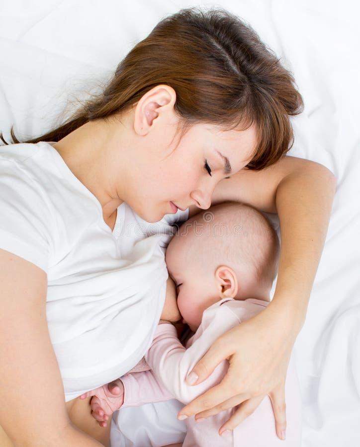 Ståenden av modern som breastfeeding henne, behandla som ett barn fotografering för bildbyråer