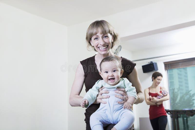 Ståenden av modern som rymmer henne, behandla som ett barn i yogastudion som ser kameran arkivbilder