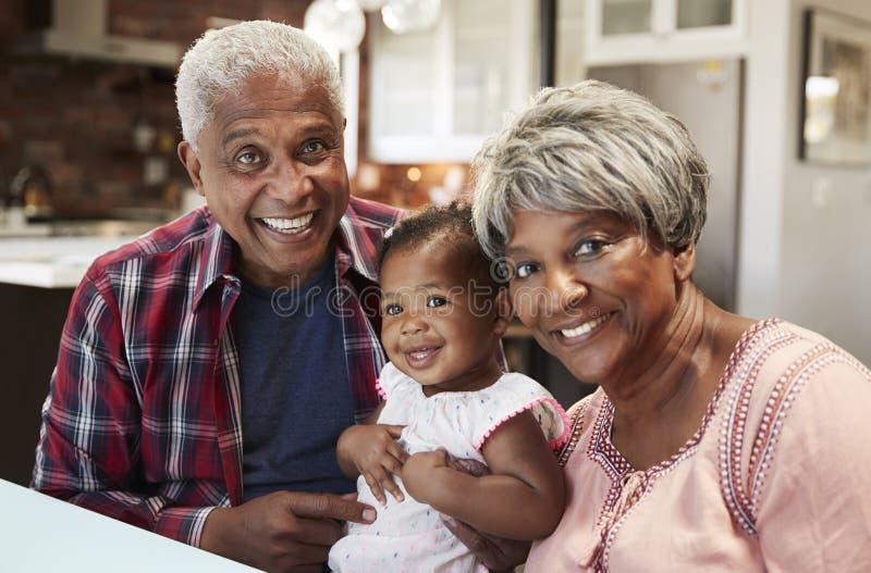 Ståenden av morföräldrar som sitter med, behandla som ett barn sondottern runt om tabellen hemma royaltyfria bilder