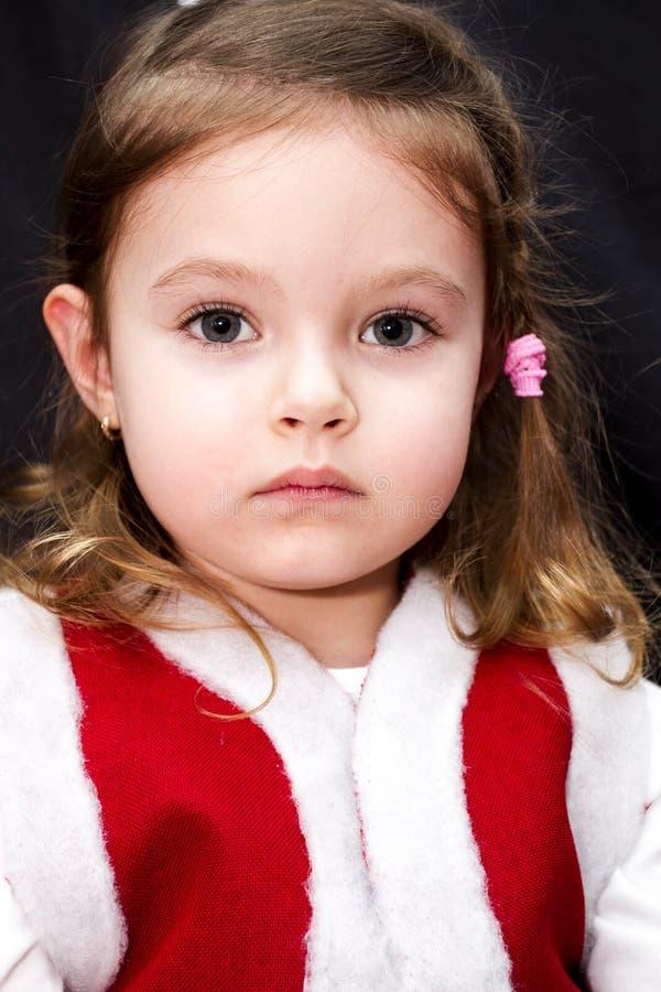 Ståenden av mycket allvarligt behandla som ett barn flickan i den röda santa klänningen fotografering för bildbyråer